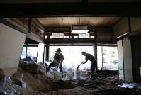 土砂が流れ込んだ家を掃除する菅廣順子さん(左)と夫の賢次さん。母の大畠祐子さん(96)を自宅で亡くした。祐子さんは着物の着付けを教えてくれたり、高齢でも自転車を乗り回すほど足腰の強い元気な人だったという=広島県坂町で2018年7月19日午前9時12分、宮武祐希撮影