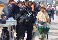 安否不明者の捜索のために集まった消防隊員らの前を通る男性=広島県坂町で2018年7月19日午前8時41分、宮武祐希撮影