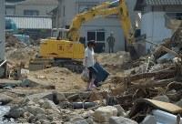 重機による安否不明者の捜索が続く中、自宅の片付けをする女性=広島県呉市で2018年7月19日午前9時37分、木葉健二撮影