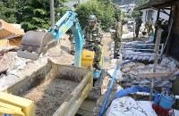 重機を使って土砂を取り除く自衛隊員ら=広島県坂町で2018年7月19日午前10時25分、宮武祐希撮影