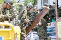 用水路に堆積した土砂や、がれきなどを取り除く自衛隊員ら=広島県坂町で2018年7月19日午前10時23分、宮武祐希撮影