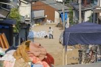 土砂が残る中、早朝に犬を散歩させる男性=広島県坂町で2018年7月19日午前7時19分、宮武祐希撮影