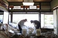 土砂が流れ込んだ家を掃除する菅廣順子さん(左)と夫の賢次さん。母の大畠祐子さん(96)を自宅で亡くした。祐子さんは着物の着付けを教えてくれたり、高齢でも自転車を乗り回すほど足腰の強い元気な人だったという=広島県坂町で2018年7月19日午前9時17分、宮武祐希撮影