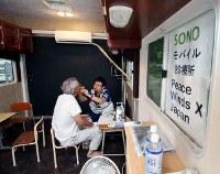 小学校に置かれたトレーラーハウスの中で夜間の診察をする医師=岡山県倉敷市真備町地区で2018年7月18日午後5時24分、幾島健太郎撮影