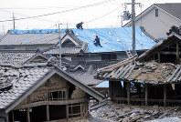 豪雨の被害を受け、ブルーシートがかけられた家屋の屋根を調べる消防隊員=岡山県倉敷市真備町地区で2018年7月19日午後1時44分、幾島健太郎撮影