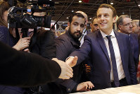 In this March 1, 2017 picture, presidential candidate Emmanuel Macron, center, flanked by his bodyguard, Alexandre Benalla, left, visits the Agriculture Fair in Paris, on March 1, 2017. (AP Photo/Christophe Ena)