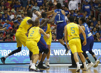 In this July 2, 2018 photo, Philippines' Jason William (7) jumps to hit Australia's Daniel Kickert, center left, as others rush to break a brawl during the FIBA World Cup qualifying basketball game at the Philippine Arena in suburban Bocaue township, Bulacan province, Philippines. (AP Photo/Bullit Marquez)