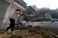 日が照りつける中、自宅に流れ込んだ土砂をかき出す人たち=広島市安芸区矢野東で2018年7月20日午前8時46分、津村豊和撮影