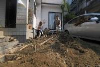 日が照りつける中、自宅に流れ込んだ土砂をかき出す人たち=広島市安芸区矢野東で2018年7月20日午前8時45分、津村豊和撮影