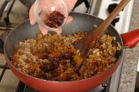 カレー粉と塩を振り混ぜて、レーズンを加える=小川昌宏撮影