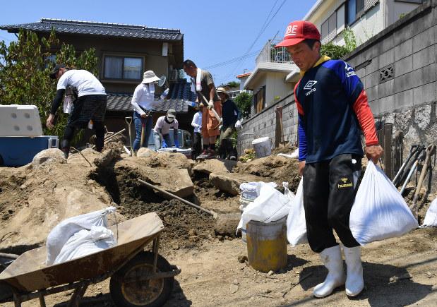 厳しい暑さが続く中、作業を続けるボランティアの人たち=広島市安芸区矢野東で2018年7月15日午後1時27分、大西岳彦撮影