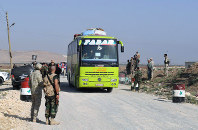 This photo released by the Syrian official news agency SANA, shows Syrian troops overseeing the evacuation of people in buses from the two pro-government villages of Foua and Kfarya, at Tel el-Eis, the crossing between Aleppo and Idlib provinces, Syria, on July 19, 2018. (SANA via AP)