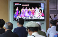 A TV screen shows a blurred photo of North Korean restaurant workers in China, during a news program at the Seoul Railway Station in Seoul, South Korea, on July 20, 2018. (AP Photo/Ahn Young-joon)