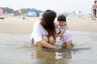 A little girl bathes in the sea for the first time in her life at Haragamaobama Beach, which opened to swimmers for the first time in eight years, in the city of Soma, Fukushima Prefecture, on July 21. (Mainichi)
