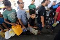 イスラエルがパレスチナ自治区ガザへの燃料供給を停止し、ガソリンスタンドで行列を作るパレスチナの人々=ガザ南部ハンユニスで17日、ロイター