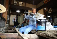 Hiroshi Nakamura removes mud from under his floor in the Hiroshima Prefecture town of Saka, on July 20, 2018. He is calling for urgent help from volunteers before the posts and the floor of his house begin to rot. (Mainichi)