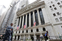In this Oct. 24, 2017, file photo, people pass the New York Stock Exchange. (AP Photo/Richard Drew)