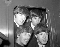 In this March 2, 1964 file photo, Britain's pop group The Beatles, from top left John Lennon, George Harrison and from bottom left, Ringo Starr and Paul McCartney pose in the window of train at Paddington Station in London. (AP Photo/Bob Dear)