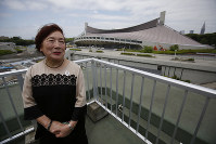 In this May 19, 2018, photo, Japanese interpreter Mariko Nagai speaks during an interview with a backdrop of Yoyogi National Stadium in Tokyo which symbolized Japan's revival just 19 years after World War II. (AP Photo/Koji Ueda)