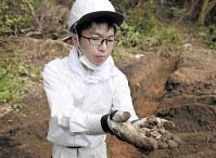 似島で被爆者の遺骨発掘調査を行う嘉陽礼文さん。後日、被爆者のものと判明した=広島市南区で2018年4月23日、山崎一輝撮影