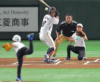 始球式で高橋叶羽さん(左)が投げた球を捕ろうとする姉陽菜さん(奥右)と審判を務めた父信也さん(同中央)=東京ドームで2018年7月21日、徳野仁子撮影