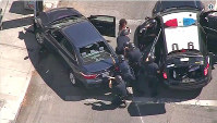 In this image from video provided by KNBC-TV, Los Angeles Police officers remove a passenger from a car that crashed after a pursuit with the driver who ran into a nearby Trader Joe's supermarket in the Silver Lake district of Los Angeles Saturday, July 21, 2018. (KNBC-TV via AP)