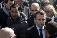 In this Wednesday April 26, 2017 file photo, Emmanuel Macron, right, is flanked by his bodyguard, Alexandre Benalla, left, outside the Whirlpool home appliance factory, in Amiens, northern France. Investigators have detained for questioning on Friday, July 20, 2018 one of President Emmanuel Macron's top security aides caught on camera beating a protester in May, a turn of events now evolving into a major political crisis for the president. The presidential Elysee Palace said it is taking steps to fire Alexandre Benalla, who was identified earlier this week by the newspaper Le Monde for beating a young protester during May Day protests while wearing a police helmet (AP Photo/Thibault Camus, File)
