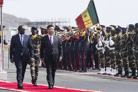 Senegal president Macky Sall, left, and Chinese President Xi Jinping, inspect the honour guard during a state visit in Dakar, Senegal, Saturday, July 21, 2018. Chinese President Xi Jinping arrived in Africa on Saturday on a four-nation visit, seeking deeper military and economic ties. (AP Photo/Xaume Olleros)