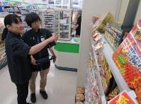 商品の陳列などを店のスタッフと確認する吉田明子さん(左)。笑顔を絶やさない姿が印象的だ=千葉県市川市のファミリーマート妙典駅西口店で