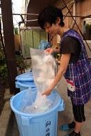 園児たちの使用済みオムツを敷地内のバケツへ捨てる保育所職員。ここから事業者が回収する=東京都文京区の向丘保育園で
