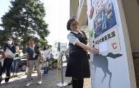 デパート前に設置した気温掲示板の数字を張り替える女性。41度を超えることを想定していなかったため、急きょ手書きで作ったという=埼玉県熊谷市で2018年7月23日午後2時33分、丸山博撮影