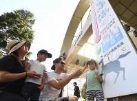 デパートの前に設置された温度掲示板で記念撮影する家族連れ。「今年は特に暑い」と話していた=埼玉県熊谷市で2018年7月23日午後3時46分、丸山博撮影