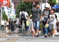 国内の最高気温を更新する41・1度を記録し、厳しい暑さの中を歩く人たち=埼玉県熊谷市で2018年7月23日午後2時48分、丸山博撮影