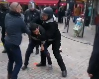 今年5月1日の労組デモで参加者に暴行を加えるヘルメット姿のベナラ容疑者(右)を捉えた動画から=AP