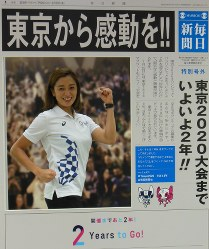 Hanae Ito, a senior Engagement and PR Planning Team project manager in the Communications Section of the Tokyo Organising Committee of the Olympic and Paralympic Games, poses behind a Mainichi Shimbun front page panel in Tokyo's Chiyoda Ward, on July 23, 2018. (Mainichi)
