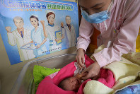 In this April 25, 2017 photo, a baby receives a vaccine shot next to a poster which reads