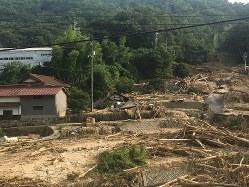 実家の向かい側の山で土砂崩れが起き、斜面は泥と流木とがれきで埋まっていた=7月13日筆者撮影