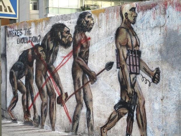 「それのどこが進化?」。サルから進化した人間が自爆ベルトをつけ銃を持って歩くようになるという壁画