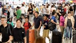 夏休みの旅行客で混み合う関西国際空港の国際線出発ロビー=2017年8月10日