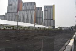 川を覆うように張られた悪臭対策のネット。奥に見える高層ビル群がアジア大会の選手村=ジャカルタで2018年7月23日、武内彩撮影