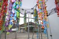 千羽鶴で飾られた献花台の奥に解体中の建物が見えた=相模原市緑区で2018年7月26日午前8時半、宮武祐希撮影