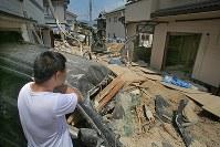 炎天下、家に流れ込んだ大量の土砂の撤去作業を昼前に切り上げ、汗をぬぐう男性=広島市安芸区矢野西で2018年7月26日午前11時56分、和田大典撮影