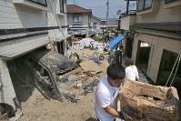 西日本豪雨で大量の土砂や流木が流れ込んだ住宅地では道や駐車場に積もった土砂が手つかずで建物から出した土を入れた土のうが積み上がる。流された車両なども動かすことができず、住民は「ボランティアも平日は来ることが希で、ここだけ取り残されたような気持ちになってしまう」と口々に話した=広島市安芸区矢野西で2018年7月26日午前11時、和田大典撮影