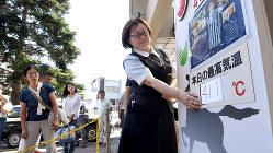 国内最高気温を更新する41・1度を記録し、百貨店前の気温掲示板の数字を張り替える女性。急きょ手書きで作ったという=埼玉県熊谷市で2018年7月23日、丸山博撮影