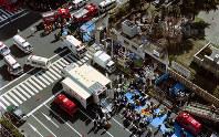地下鉄築地駅から地上に出て倒れたサリン中毒症の乗客を救助する救急隊員=東京都中央区築地で1995年3月20日、本社ヘリから山下浩一撮影