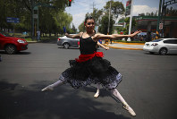 A ballerina dances at a traffic light stop, in Mexico City, Saturday, July 28, 2018. In this sprawling megalopolis notorious for its clogged streets, a theater company sent out tutu-clad dancers out to delight motorists at snarled intersections with snippets from ballet classics like The Nutcracker and Swan Lake all in the 58 seconds it takes for the light to go from red to green. (AP Photo/Emilio Espejel)