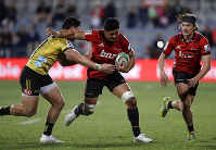 Crusaders Pete Samu runs at Hurricanes Ben Lam, left, as teammate George Bridge, right, watches during their Super Rugby semifinal in Christchurch, New Zealand, on Saturday, July 28, 2018. (AP Photo/Mark Baker)
