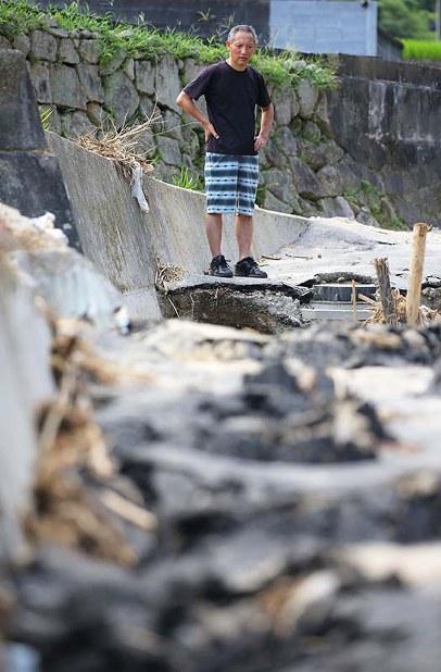 妻の圭子さんが濁流に流されたと思われる場所に立つ、夫の伊藤徳幸さん=広島県海田町で2018年7月21日、宮武祐希撮影