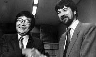 最高裁判決後、作家の佐木隆三さんと握手して喜ぶローレンス・レペタさん(右)