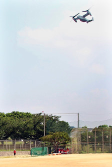 A U.S. Air Force CV-22 Osprey flies over Futenma No. 2 Elementary School as students play baseball in the playground in Ginowan, Okinawa Prefecture, on July 26, 2018. (Mainichi)